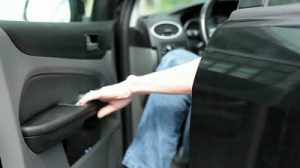 stock-footage-caucasian-man-opening-car-door-and-sitting-in-the-black-land-vehicle